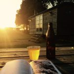 Photograph bottle nettle beer on picnic table outside shepherd hut with sunset