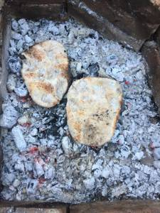 photo of flat breads cooked directly on campfire coals